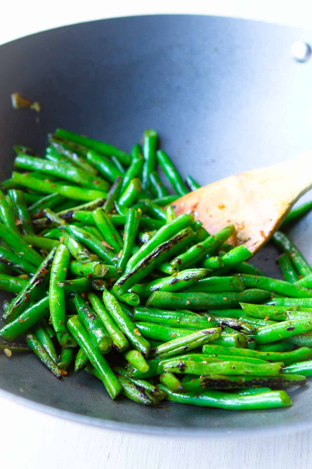 Green beans in a nonstick wok with a wooden spoon.
