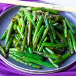 Stir fried green beans and chopsticks on a gray plate, sitting on a purple napkin.