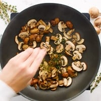 Adding thyme to mushrooms in skillet.