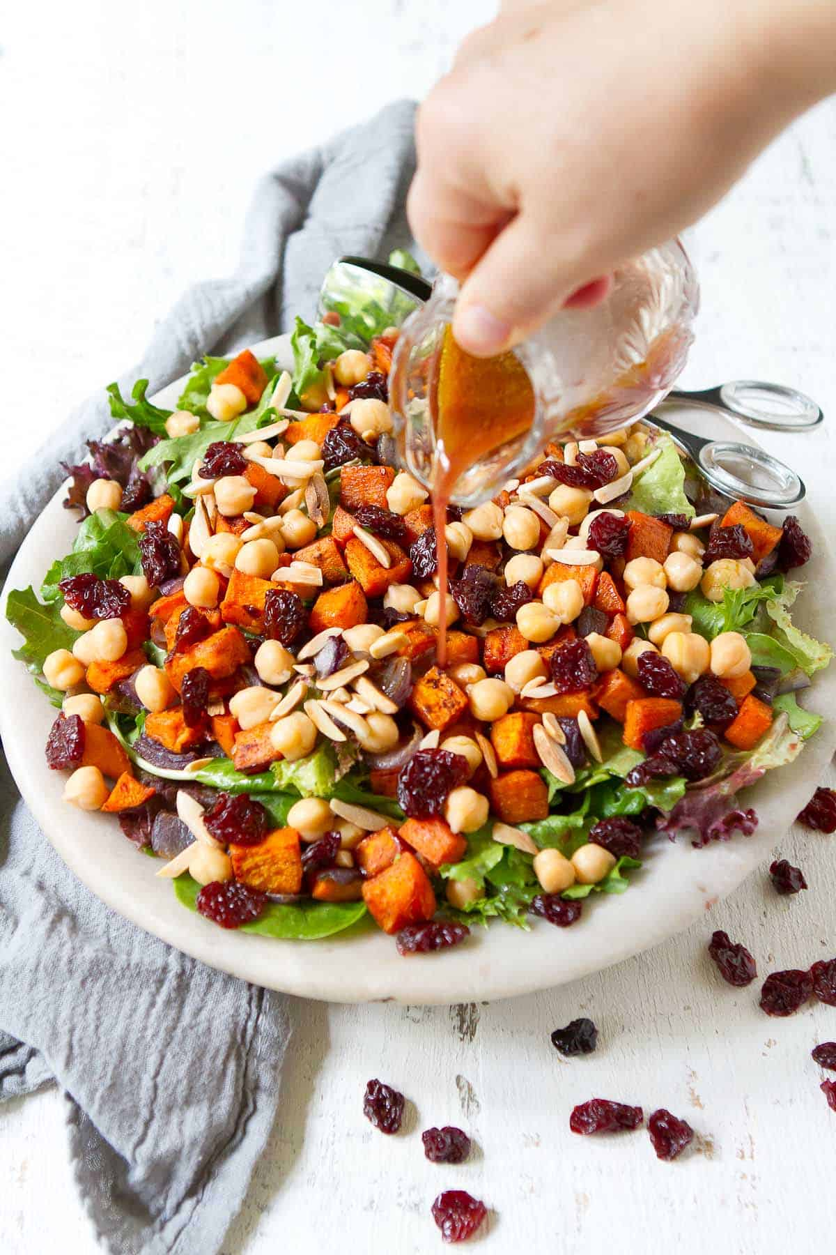 Pouring dressing over salad with sweet potato, tart cherries, greens and chickpeas.