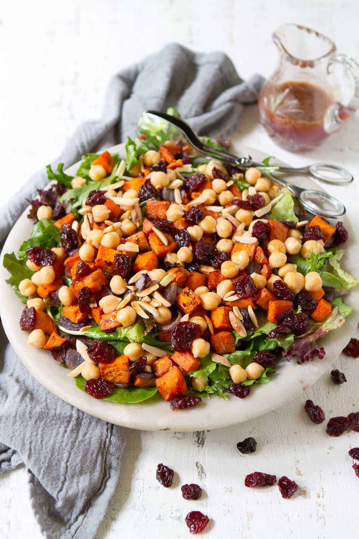 Sweet potato salad with chickpeas and tart cherries in stone bowl. Carafe of dressing behind.