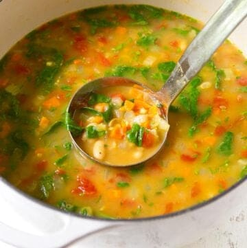 White bean soup in a large white saucepan with silver ladle.