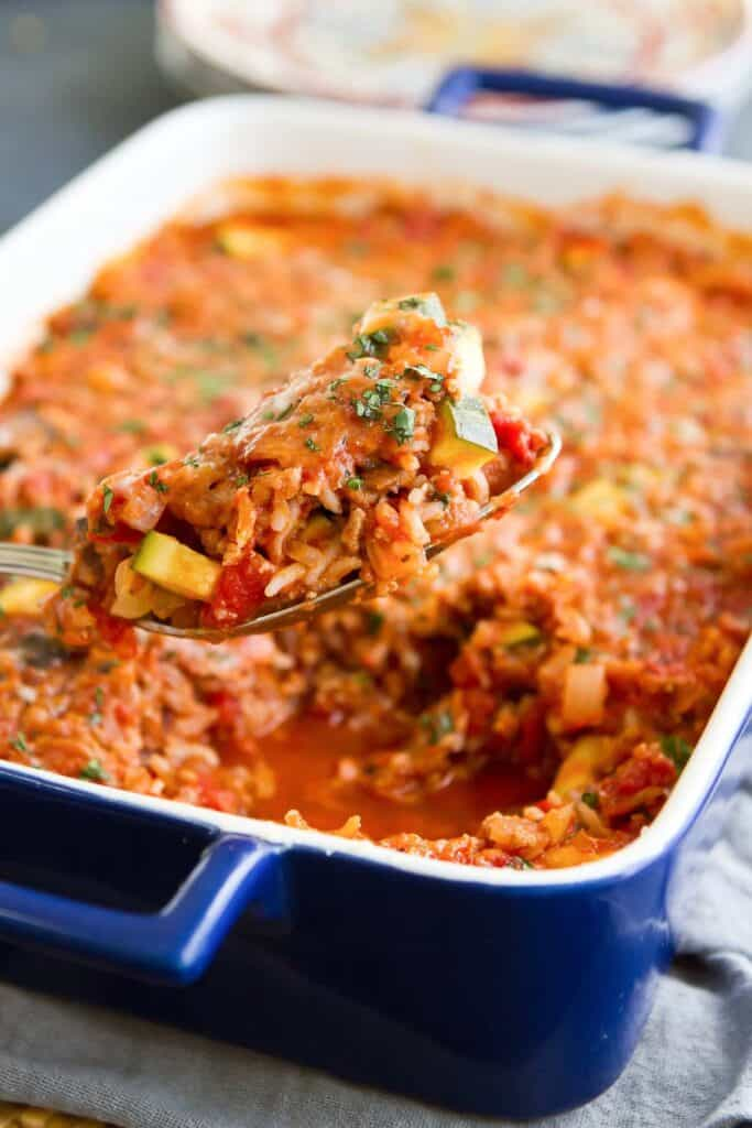 Spoon scooping out turkey, zucchini and rice casserole from baking dish.
