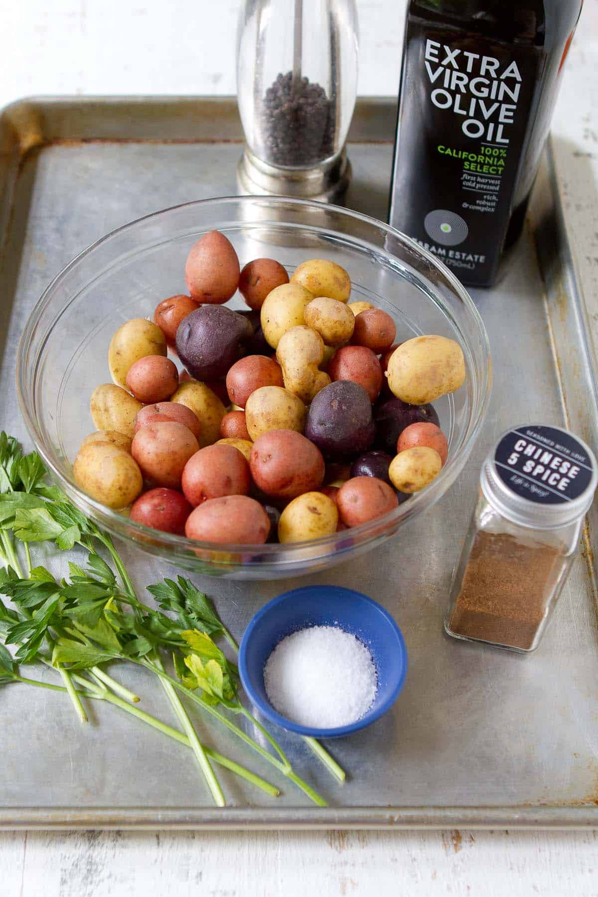 Ingredients for roasted potatoes on a baking sheet.