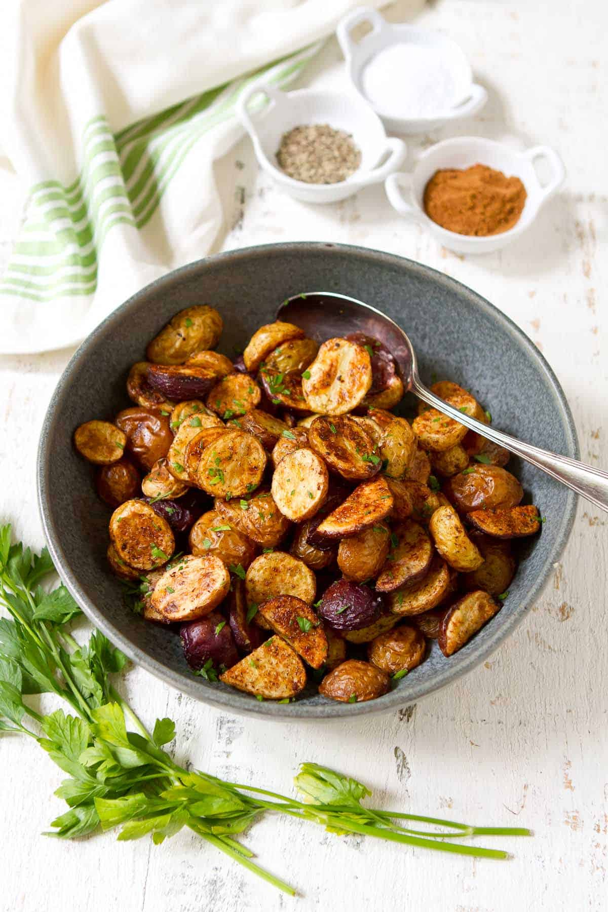 Roasted mini potatoes and spoon in a gray bowl. Parsley and seasonings on the side.