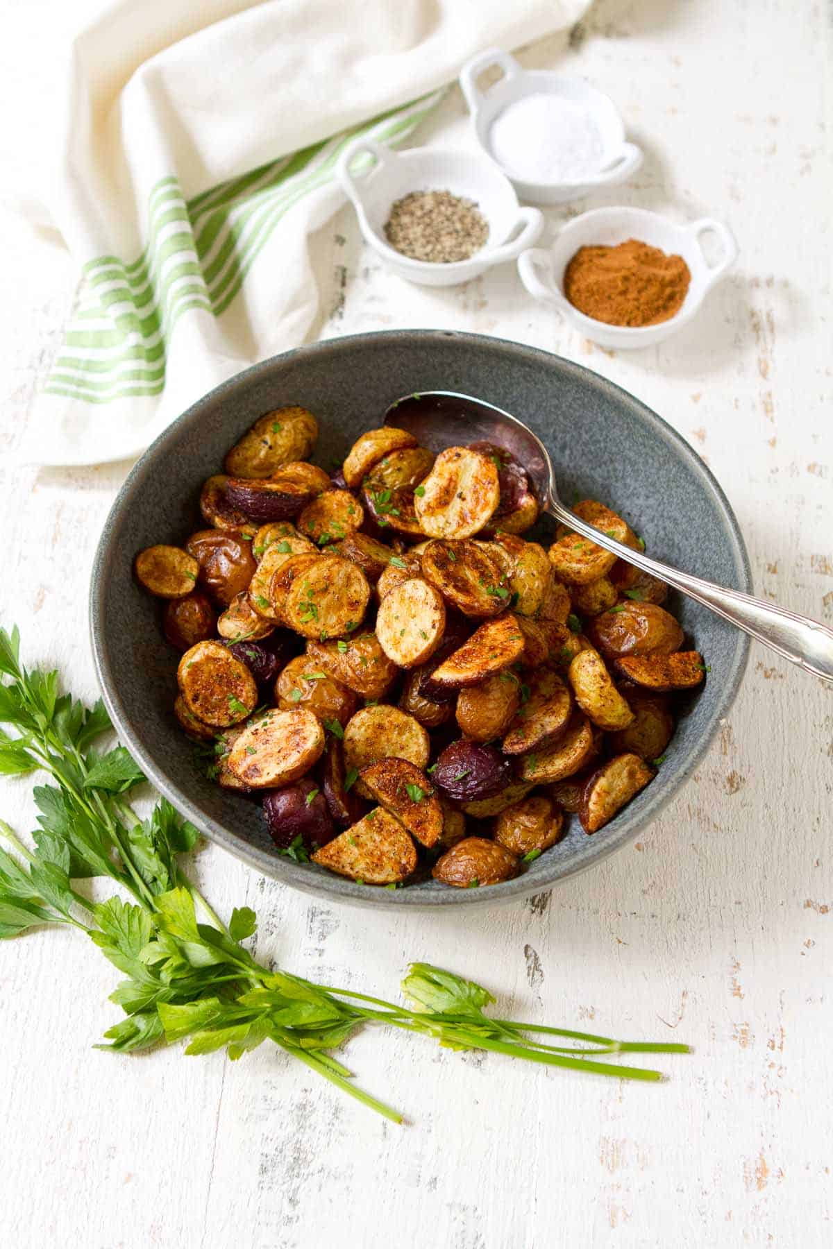 Overhead photo of mini roasted potatoes in a gray bowl, seasonings in small white bowls.