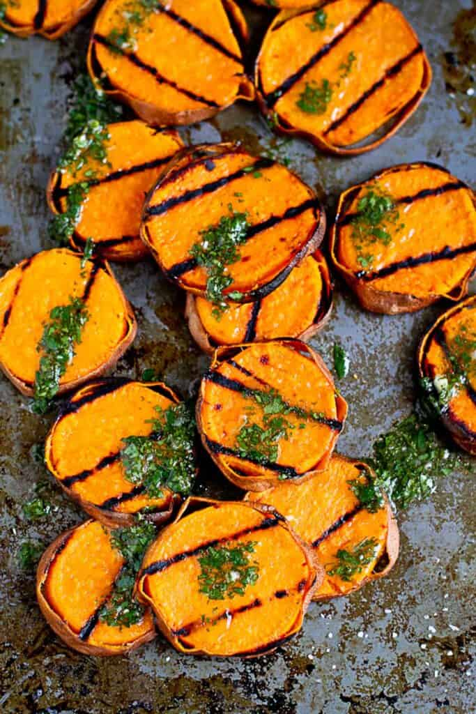 Grilled slices of sweet potato with green sauce on baking sheet.