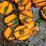 Sweet potato slices and cilantro vinaigrette on baking sheet.