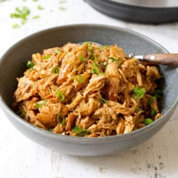Shredded hoisin Instant Pot chicken breasts in a gray bowl, garnished with green onions.