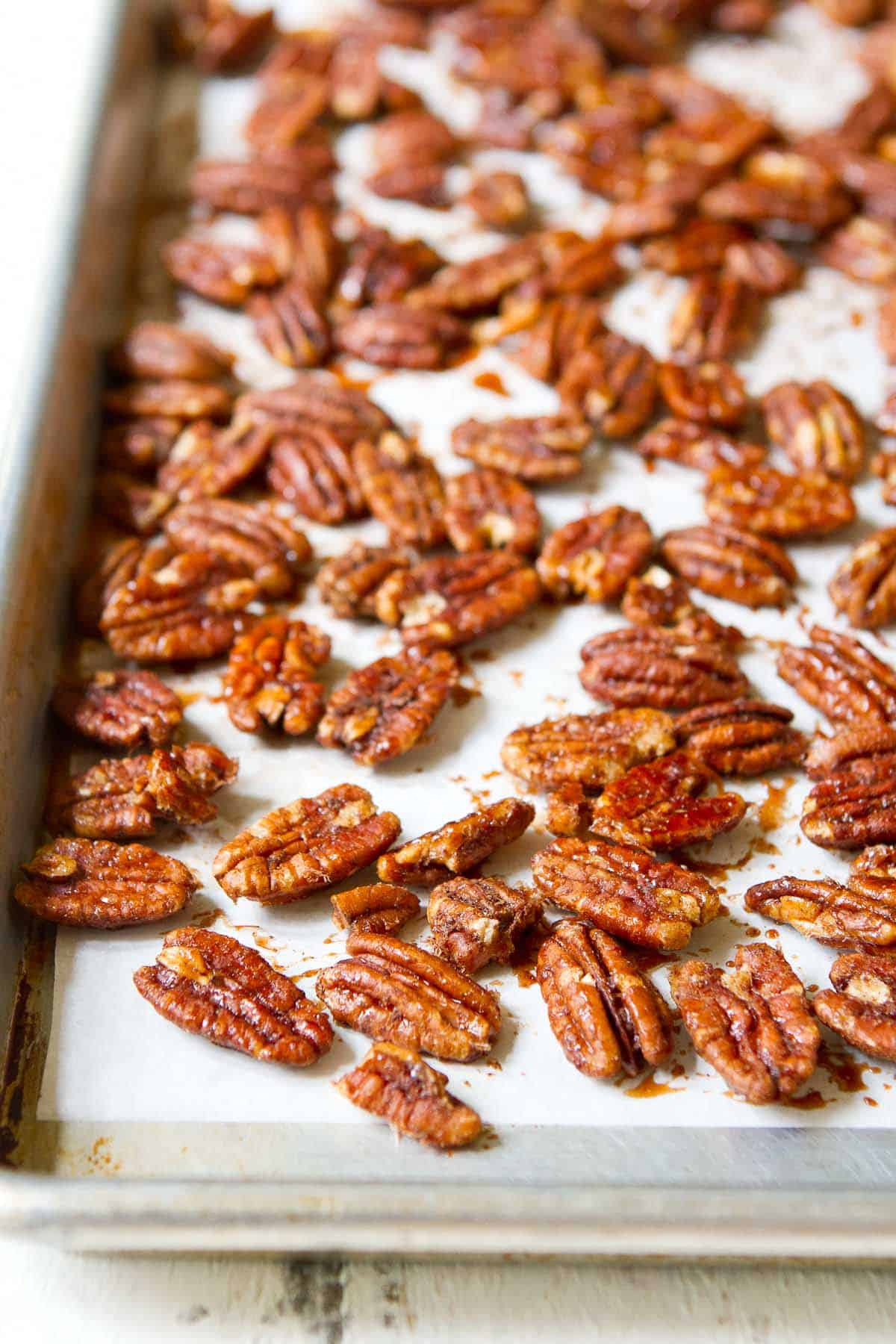 Maple syrup glazed pecans on a baking sheet.