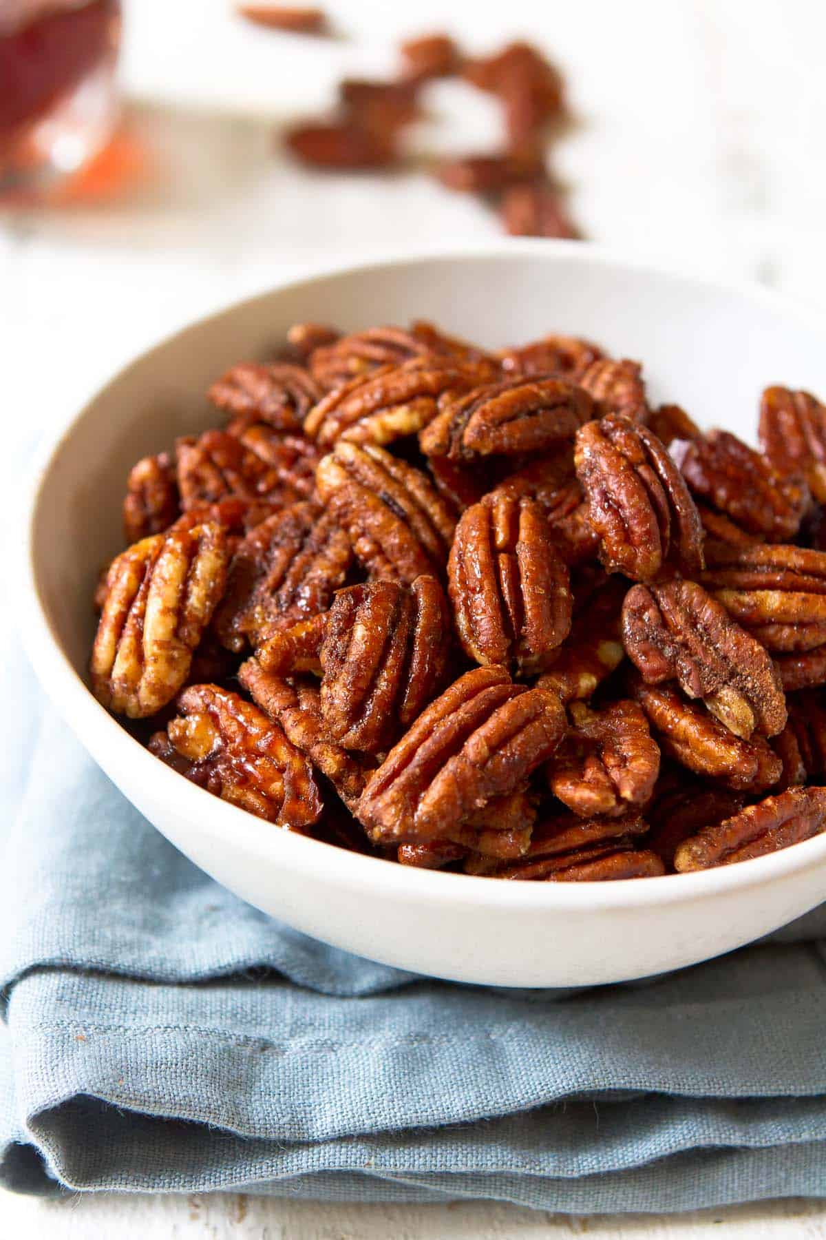 A white bowl filled with maple candied pecans.