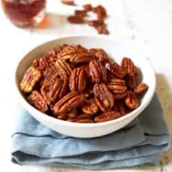 Maple pecans in a white bowl, sitting on a blue napkin.