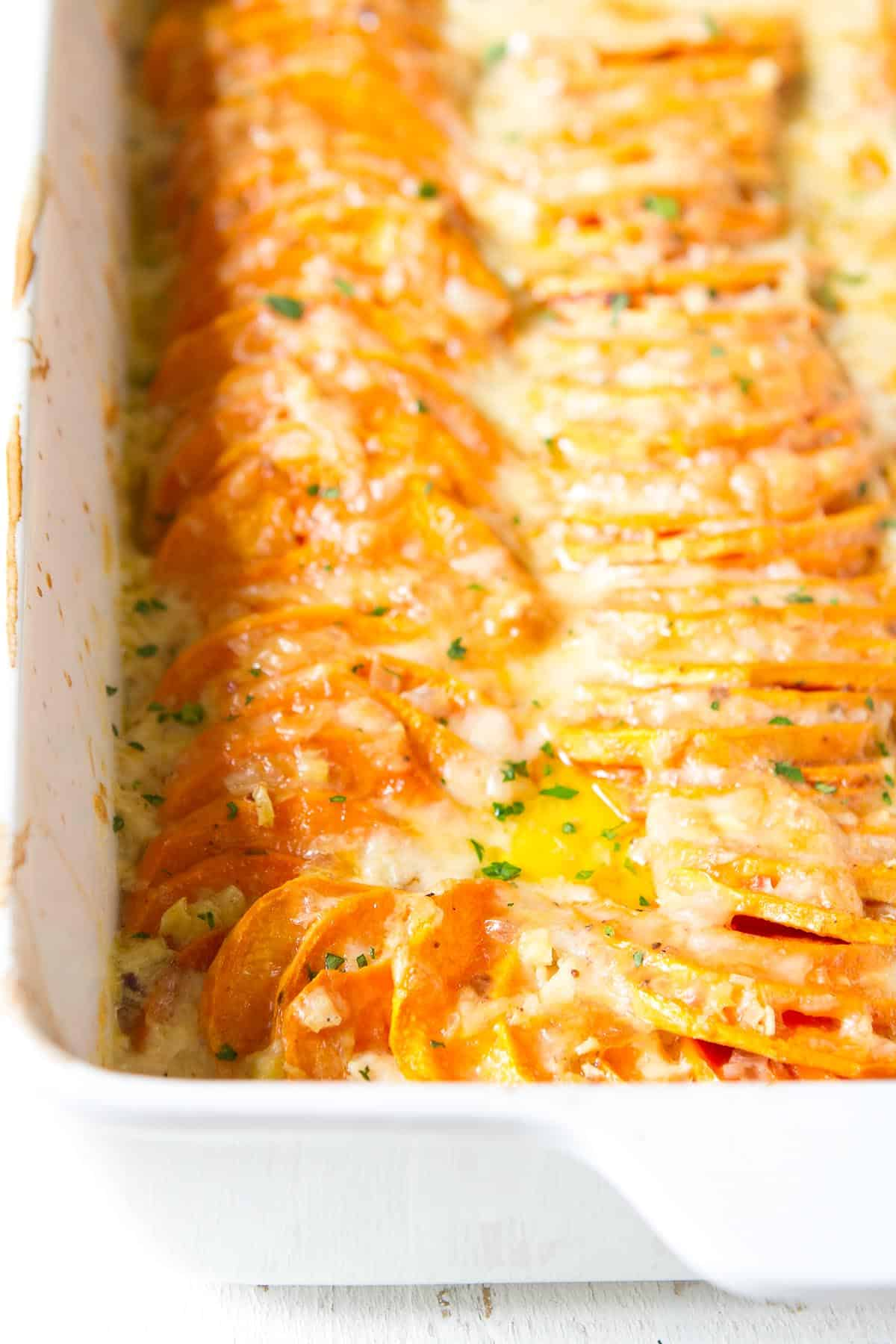 Rows of cooked sweet potatoes, topped with cheese sauce and melted cheese.