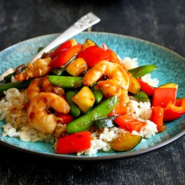 Shrimp stir fry with vegetables on a blue plate and a white plate.