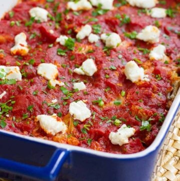 Blue casserole dish with cauliflower, tomato sauce and goat cheese.